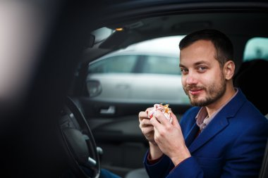 Handsome young man eating a hurried lunch in his car