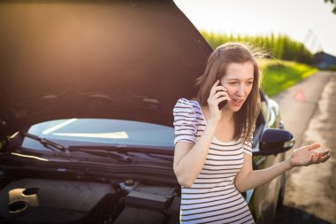 Woman calling the roadside service, assistance