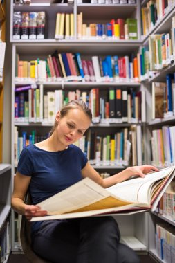Woman studying an old book in archives