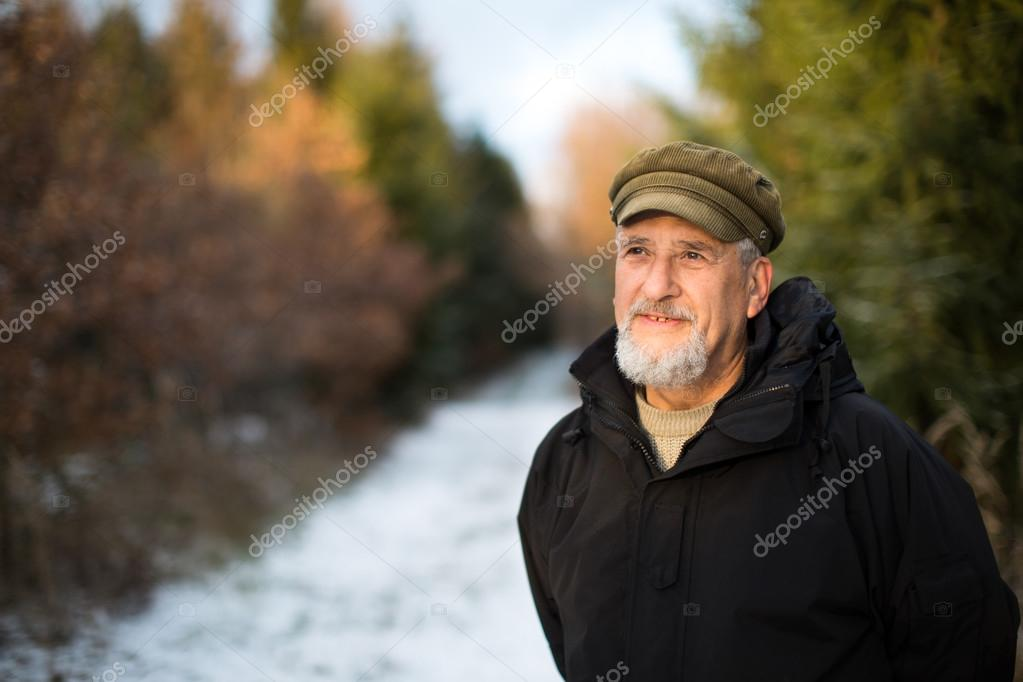Senior man, outdoor on a snowy forest path