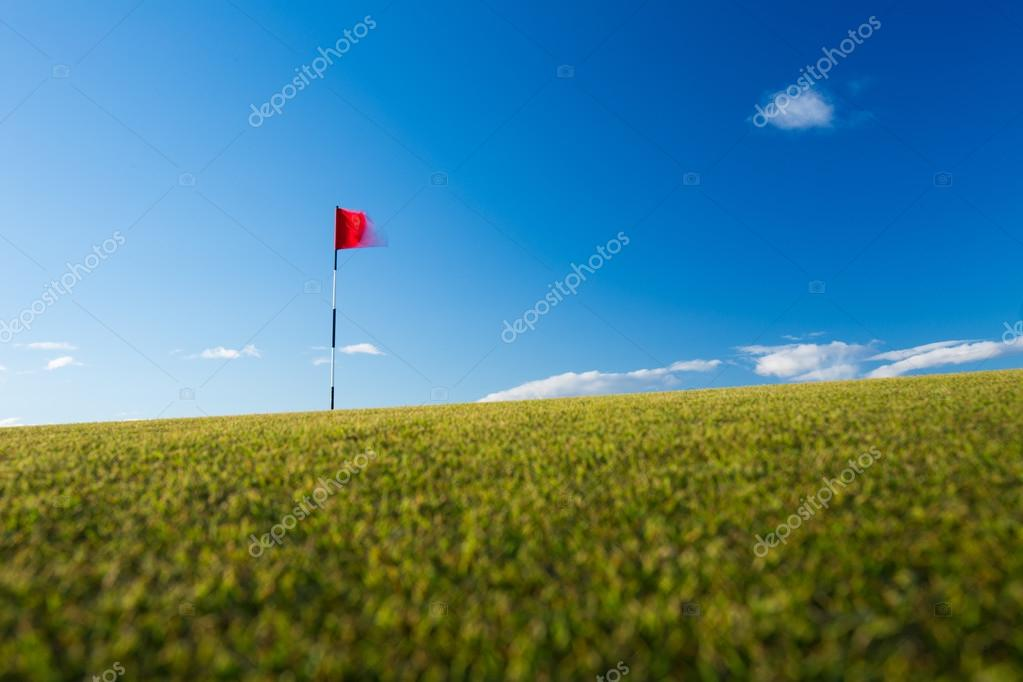 Red golf flag on a golf course