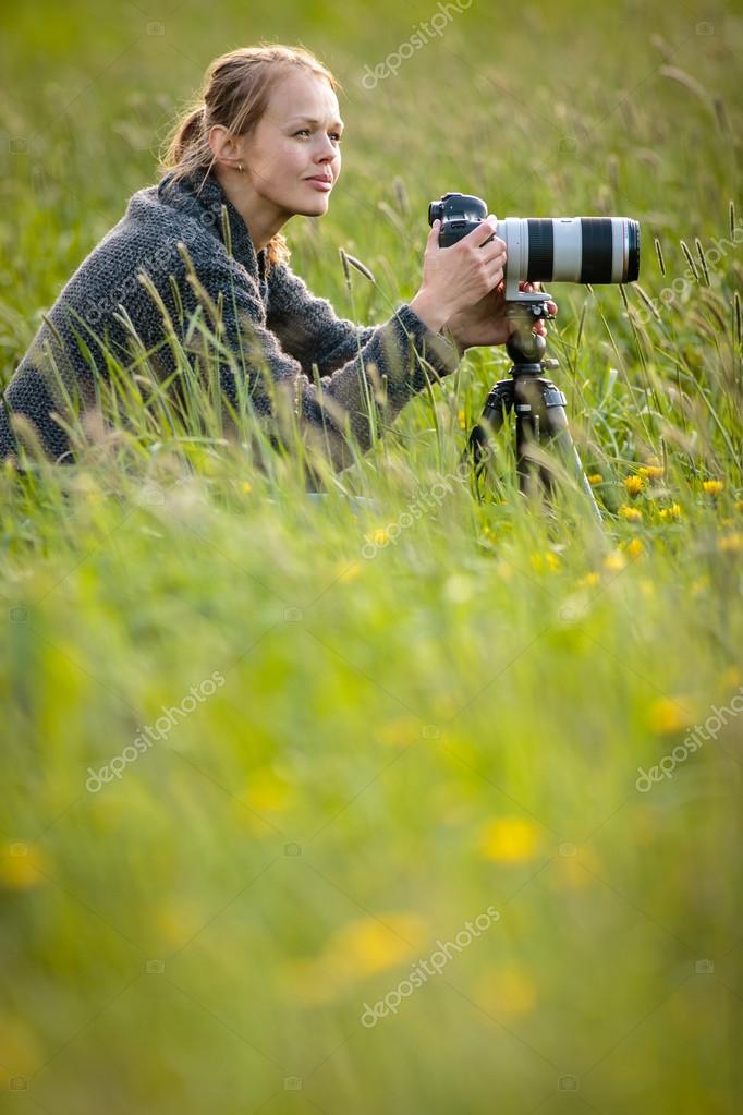 Pretty young woman with a DSLR camera outdoors, using a tripod,