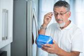 Ist das noch in Ordnung? Senior Mann in seiner Küche am Kühlschrank