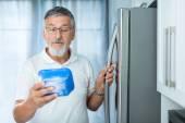 Fotografie Ist das noch in Ordnung? Seniorchef in seiner Küche am Kühlschrank
