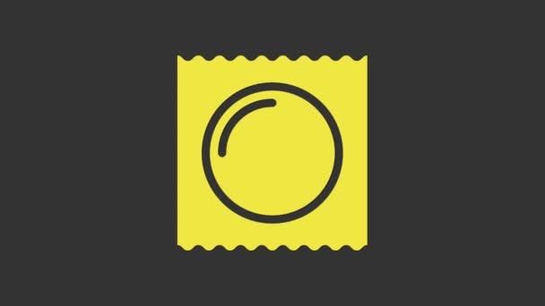 Gelbes Kondom im verpackungssicheren Sexsymbol isoliert auf grauem Hintergrund. Sicheres Liebessymbol. Verhütungsmethode für Männer. 4K Video Motion Grafik Animation