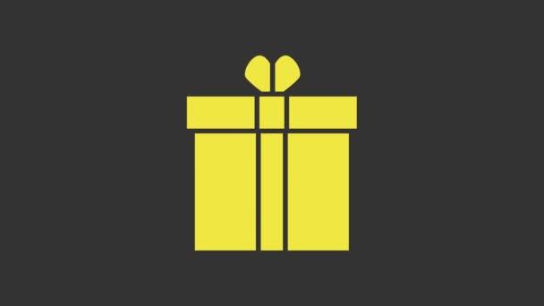 Sárga Ajándék doboz és szív ikon elszigetelt szürke háttér. Valentin nap. 4K Videó mozgás grafikus animáció