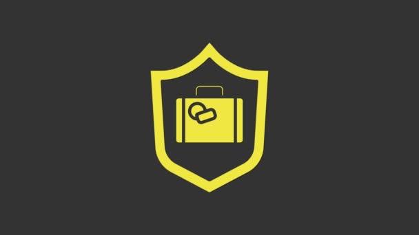 Sárga utazási bőrönd pajzs ikon elszigetelt szürke alapon. Utasbiztosítás. Biztonság, biztonság, védelem, védelem. 4K Videó mozgás grafikus animáció