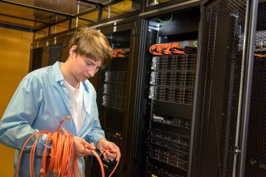 Datacenter engineer rolling up network cables
