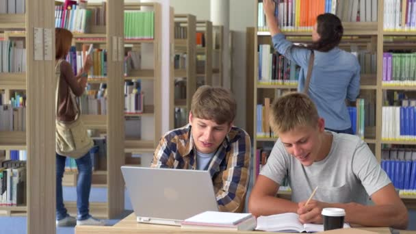 Two students studying in college library and smiling at camera