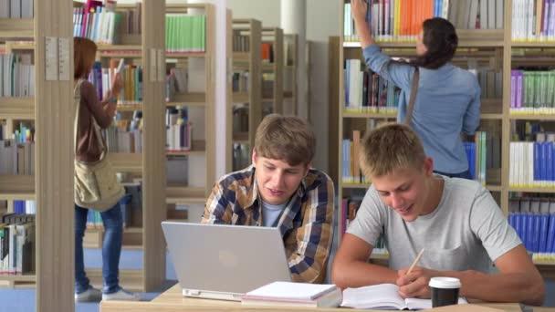 Dva studenti studují v univerzitní knihovnou a usmívá se na kameru