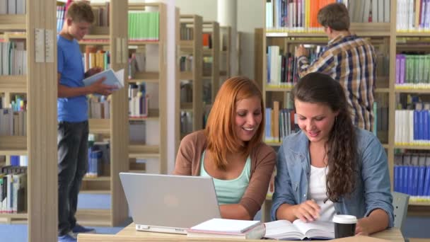 Two smiling students girls in library with laptop and books