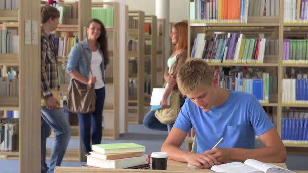 Sportive studenta chlapec učení psacího stolu v knihovně školy