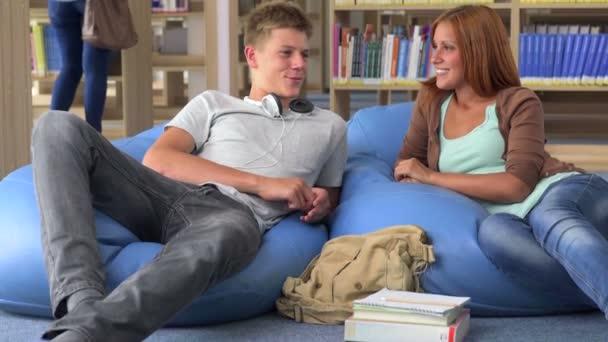 Dva studenti spolužák relaxační na beanbag college Library