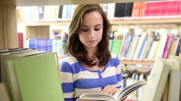 Dolly shot through bookshelf of happy student
