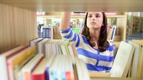 Studentka odběr knihy ze školní knihovny, police