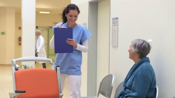 Sestra plnění pacientů souboru a pomáhá jí na vozíku