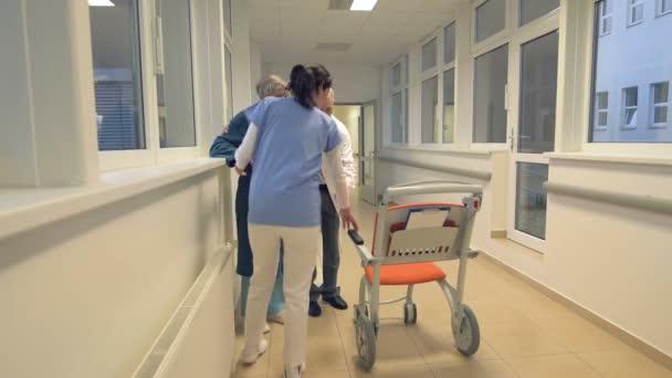 Lékařský tým pomáhá pacientovi sedět na vozíku