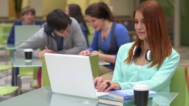 Studentka studovat s notebookem v učebně se spolužáky