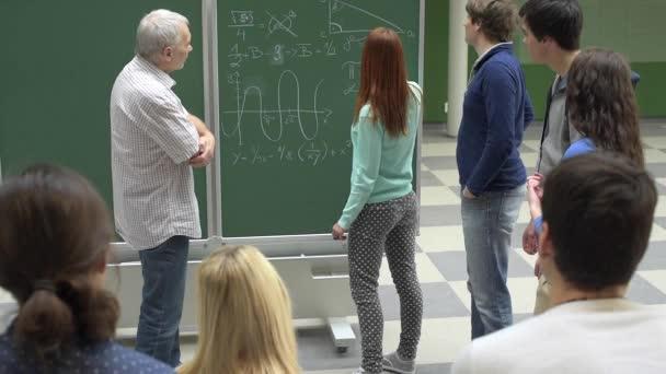 Spolužáci s profesorem psaní matematiky zkoušku