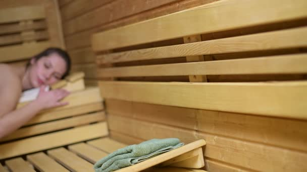 Woman relaxing and leaving sauna cabin