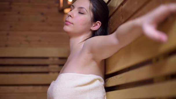 Frau sitzt und entspannt in Saunakabine