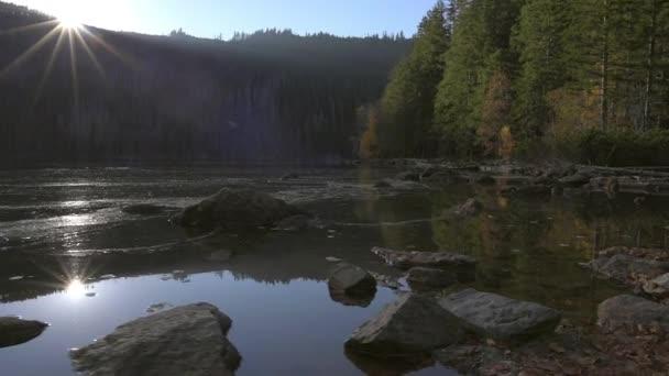 Podzimní západ slunce od břehu jezera v horách