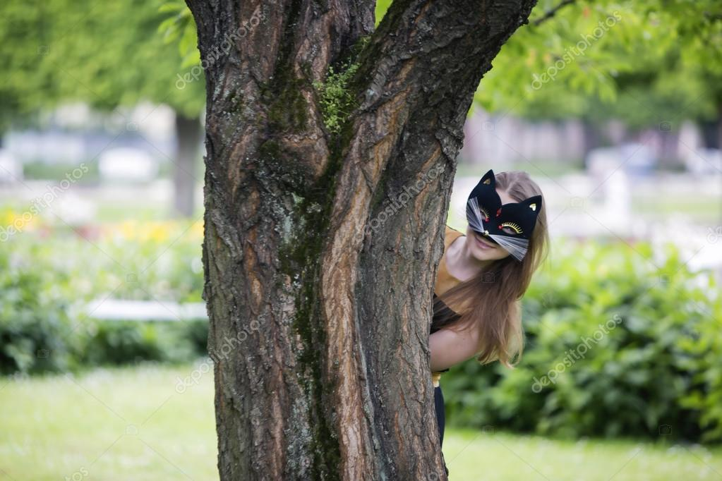 Woman  with mask hiding behind oak stem