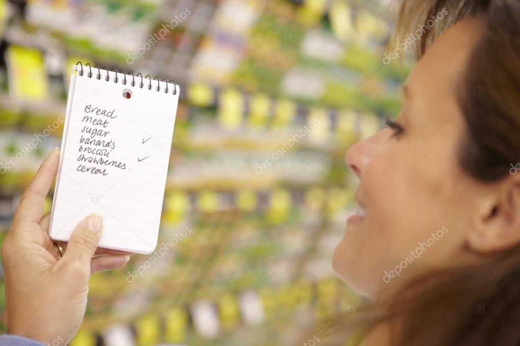 mujer mirando lista de supermercado de compras fotos de stock