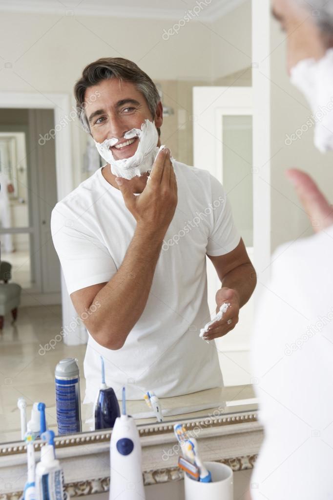 Homme dans la salle de bain miroir de rasage for Salle de bain homme