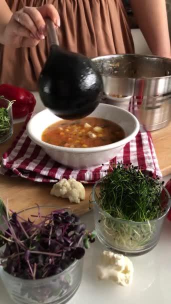 Nalévání polévky z hrnce do talíře pomocí naběračky