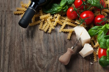 italian food with raw fusilli, tomato, basil, cheese
