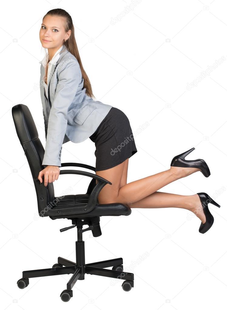Empresaria de rodillas en la silla de la oficina mirando for Silla ergonomica rodillas