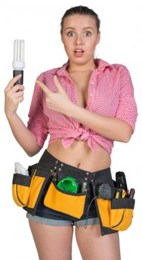 Woman in tool belt holding energy-saving lamp