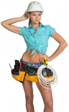 Pretty electrician in helmet, shorts, shirt, tool belt with tools and electric cable