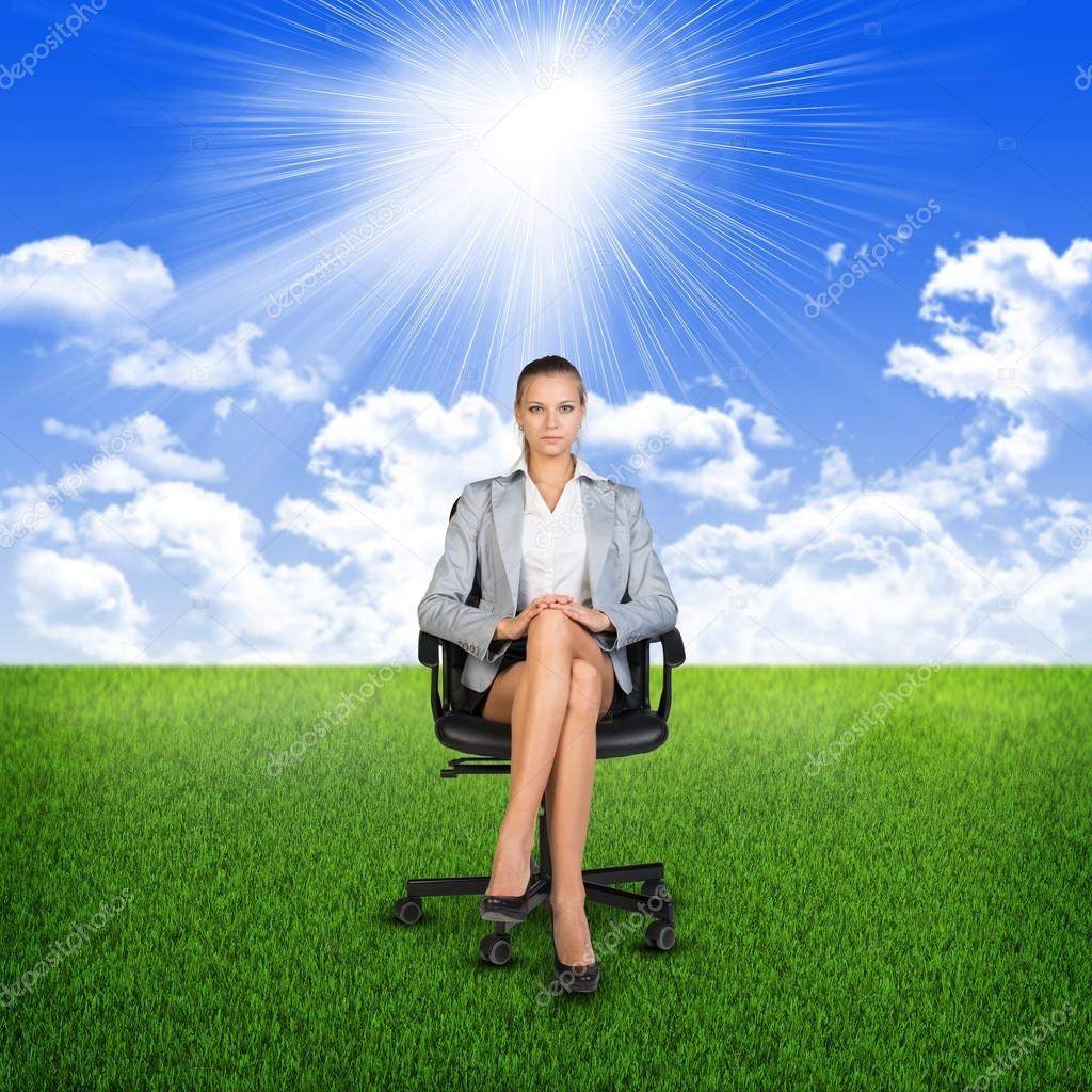 Businesswoman sitting on the chair on nature
