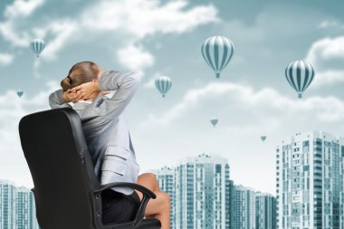 Businesswoman sitting backwards on chair relaxed