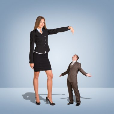 Businesswoman Pointing to small Businessman.