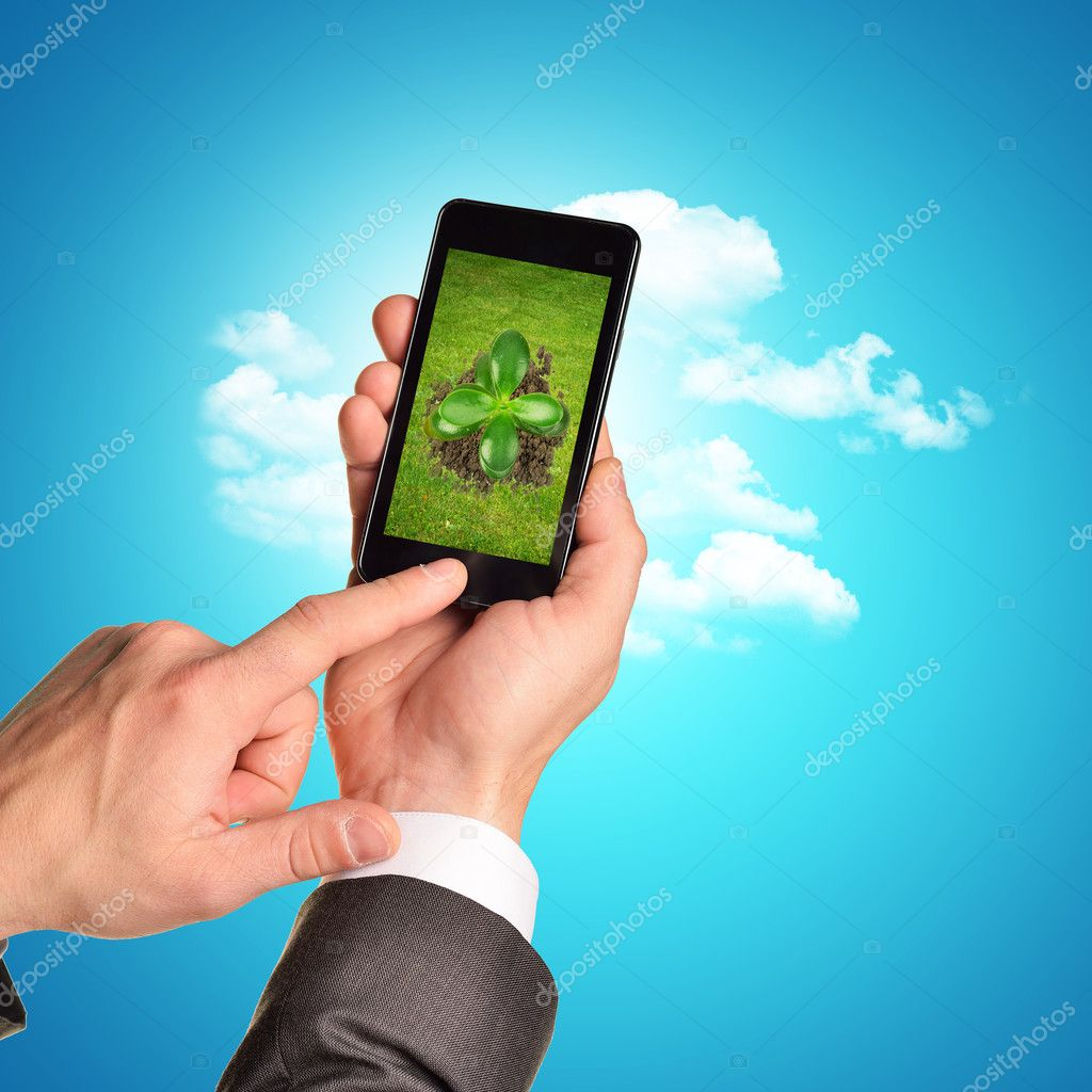 Businessman holding phone with plant