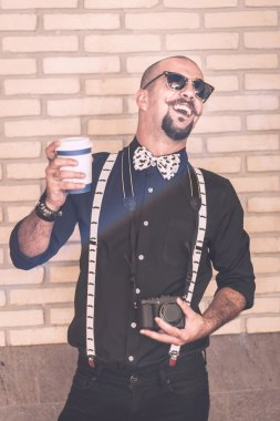 Pretentious hipster having an annoying laughter wile holding his coffee and his camera
