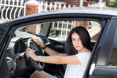 Woman in her late 30s to early 40s in a car happy to have passed the driver license test