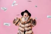 Verspielter kleiner Junge im Pelzmantel macht Rockn Roll-Geste im Geldregen