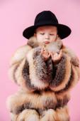Netter kleiner Junge in Pelzmantel und klassischem Hut, der Rockn Roll Geste macht