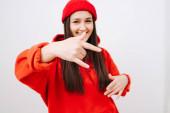 Kichernde junge Frau in leuchtend roter Mütze und Kapuzenpulli, die eine Rock n Roll-Geste macht. Sie hat seitlich lange glatte Haare. Drinnen, vor der weißen Wand. Selektiver Fokus auf ihre Hand