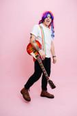 Silly-Rockmusiker posiert mit seinem Instrument. Er trägt eine regenbogenfarbene Perücke, Sonnenbrille und eine rote Gitarre auf der Schulter. Vor rosa Hintergrund