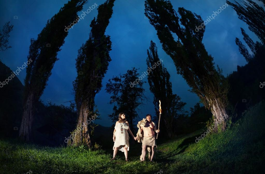 Caveman couple in dark forest
