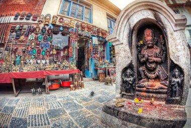 Hindu statue near the shop selling masks and souvenirs on the square near Swayambhunath stupa in Kathmandu valley, Nepal stock vector