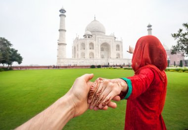 Woman in red Indian costume holding her friend by hand and pointing to Taj Mahal in Agra, Uttar Pradesh, India stock vector