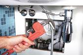 Fotografie Reparatur eines Rohres unter einem Waschbecken