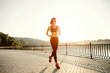 Running woman. Runner jogging in sunny bright light. Female fitn