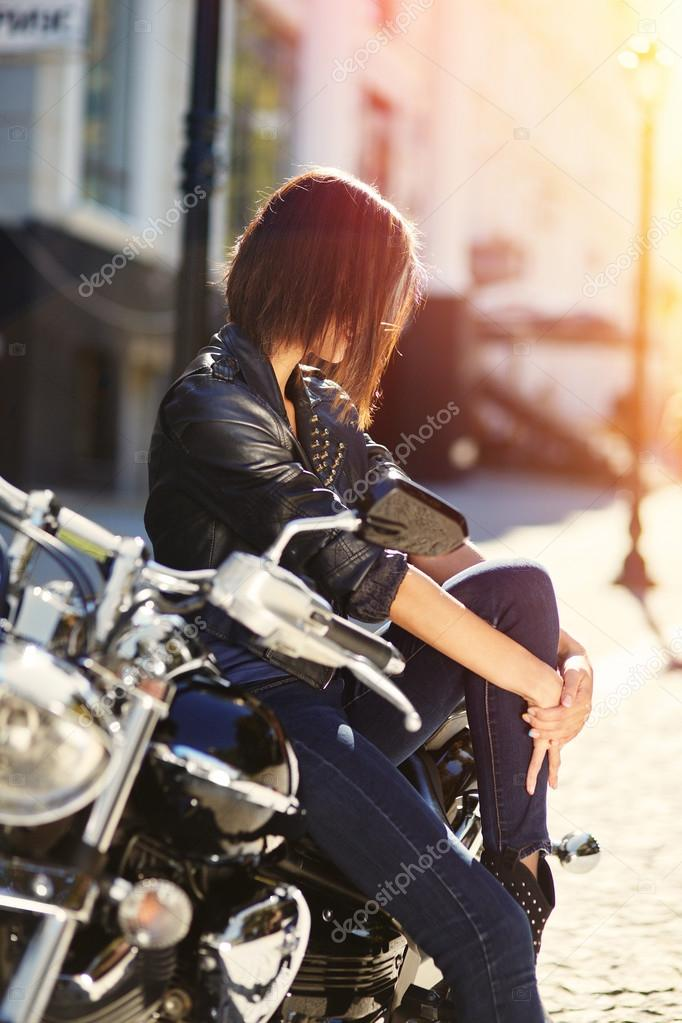Biker girl in a leather jacket on a motorcycle